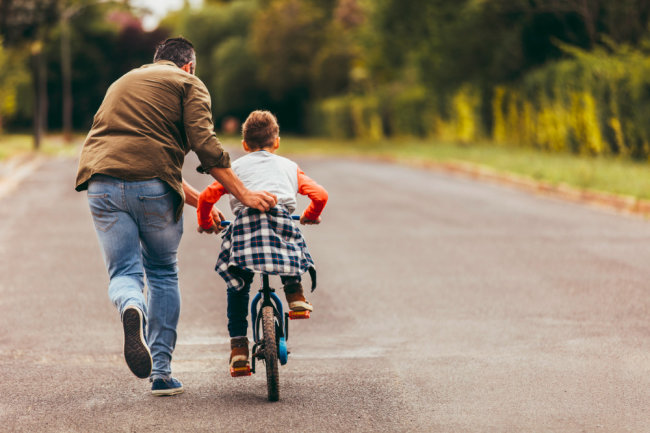 man helping his kid in learning to ride a bicycle picture id1140118229 t 650x433